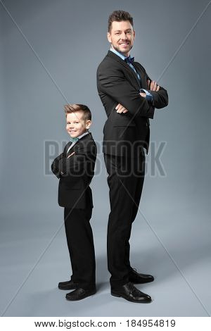 Father and son dressed in suits on color background