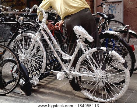 Bicycles parked in the bicycle rack. A bicycle was wrapped in the foil.