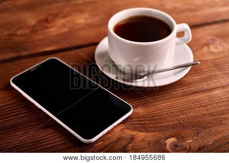 Coffee And Mobile Phone. Smartphone And A Cup Of Espresso On A Wooden Table. The Gadget. Coffee Hous