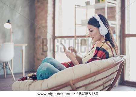 Portrait Of Beautiful Happy Latin Girl Sitting In Stylish Armchair At Home With Phone And Listen To