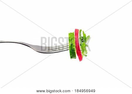 Slice cucumber radish and parsley impaled on fork isolated on white background close-up view.
