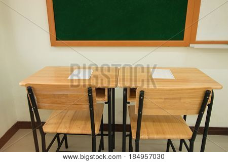 test paper on wood table of classroom and greenboard in secondary education