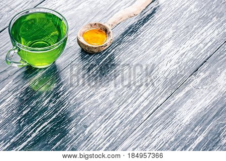 Green mint tea in translucent glass tea cup with honey on textured black wood background
