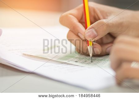 students hand testing doing examination with pencil drawing selected choice on answer sheets in school exam at college