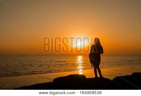 Silhouette of young woman standing alone lonly by the sunset light of sea