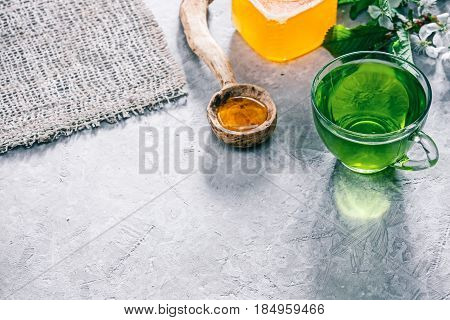 Green mint tea in translucent glass tea cup and honey in rustic spoon on concrete background with blossom twig of pear tree