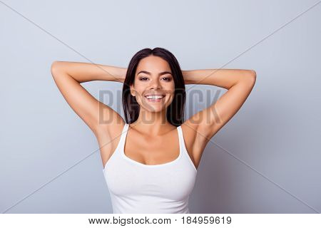 Portrait of a cute mulatto in casual clothes standing on the blue background. She is cheerful and relaxed
