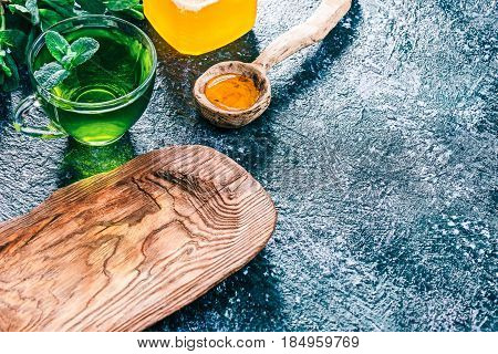 Green mint tea in translucent glass tea cup and honey in rustic wooden spoon on textured spotty background with fresh mint and rustic wooden plate