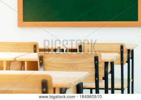 School empty classroom with desks chair wood with greenboard in high school education concept