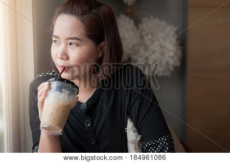 Young Asian woman drinking iced latte coffee beside window in cafe with good feeling. Weekend lifestyle abstract concept