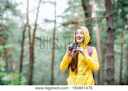 Young woman in yellow raincoat looking with binoculars in the green pine forest. Bird watching in the forest