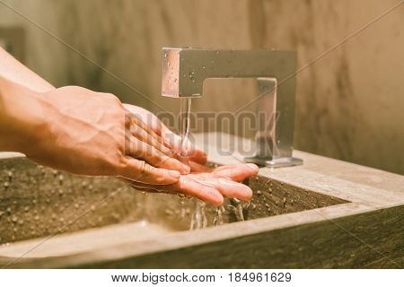 Man washing hands in public restroom. Modern WC sanitary or hygienic healthy lifestyle concept