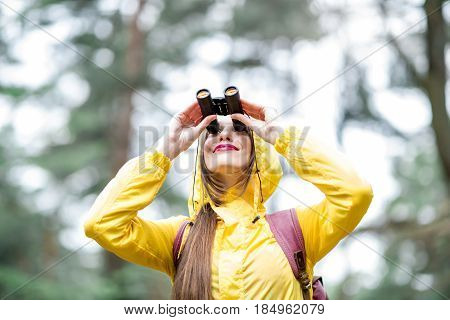 Young woman in yellow raincoat looking with binoculars in the green pine forest. Bird watching concept