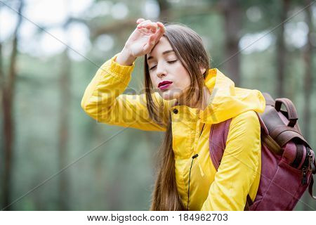 Tired woman in yellow raincoat with headache during the travel in the green forest