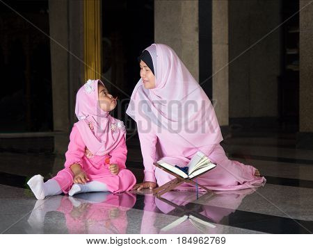 happy muslim girl with full hijab in pink dress asian traditonal style dress learning holy Quran book.