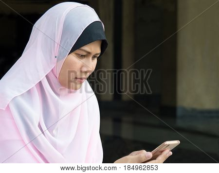 happy muslim woman with full hijab in pink dress asian traditonal style dress using smart phone