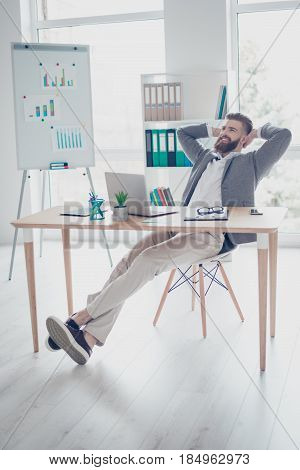 Vertical Photo Of Satisfied Happy Young Bearded Man In Formalwear Having A Rest While Sitting On A C