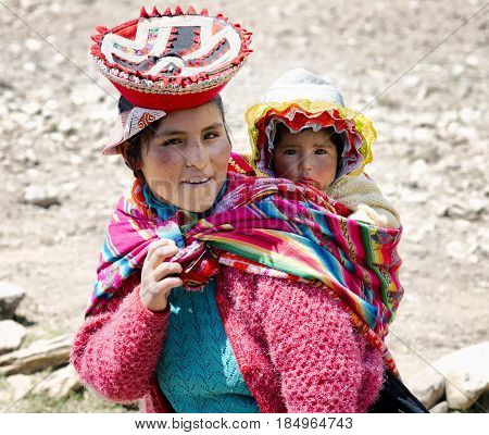 Close up portrait of a smiling Quechua woman dressed in colourful traditional handmade outfit and carrying her baby in a sling. October 21 2012 - Patachancha Cuzco Peru