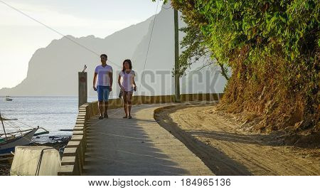 People Walking On Road With The Sea