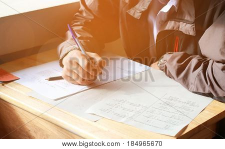 boy student testing in exercise paper exams answer sheets on wood table in classroom
