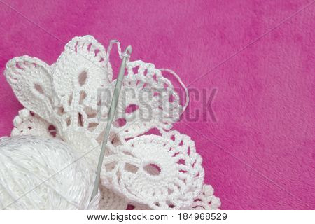 White vintage doily. Cotton yarn for knitting and crochet hook. Photo of crochet process on the pink background