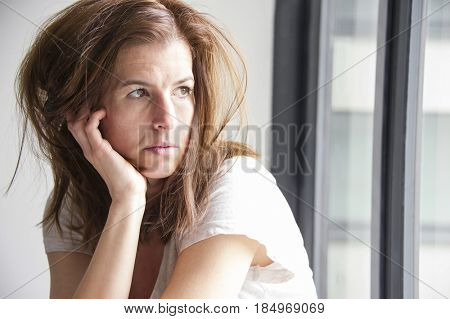 Tired and sad woman is sitting in the window seat, looking through the glass. Depression concept.