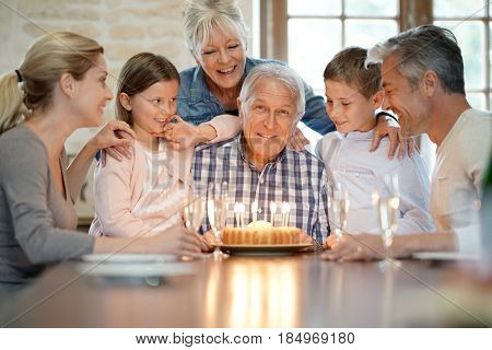 Family celebrating grandfather birthday with cake and candles