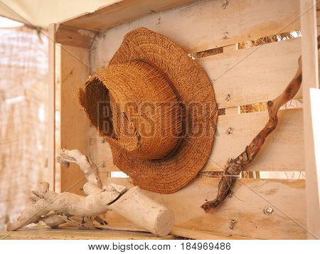 Old and broken straw hat, wooden box and branches.
