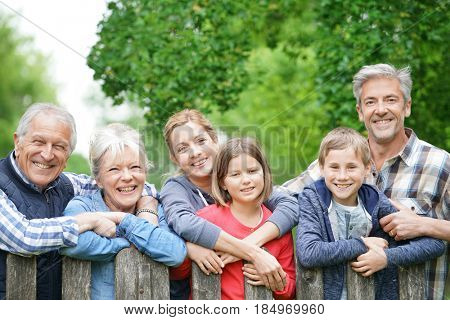 Portrait of happy family leaning on fence