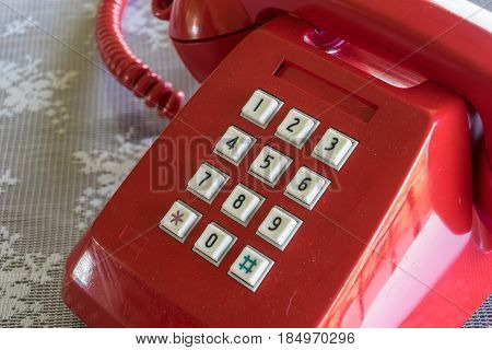 Red old telephone and white key pad