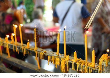 people lighing incense to pray from they faith in buddhism