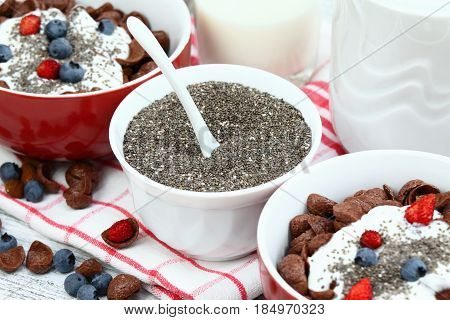 Breakfast chocolate cereal cornflakes with yogurt and chia seeds. Sweet breakfast crunchy cereals in a bowl