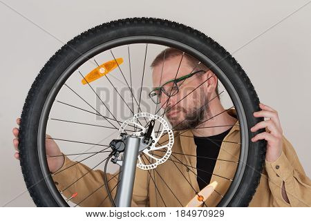 Bearded Man Checks The Fastening Of The Front Wheel