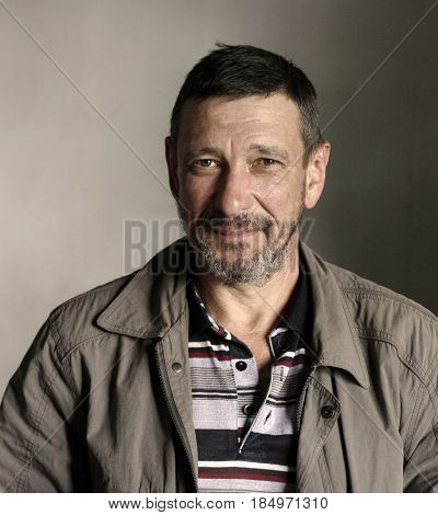 Portrait of bearded 50-year-old man with mocking face in sloppy casual clothes on a gray background grunge style