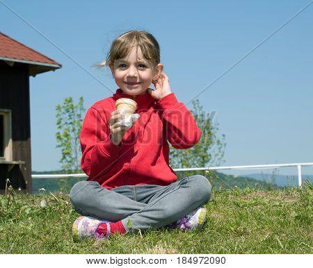 Little smilling girl eating icecream sit on grass