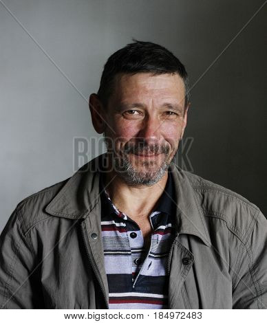 Smiling man with a red weather-beaten face and a gray beard in simple casual clothes on a gray background in style grunge