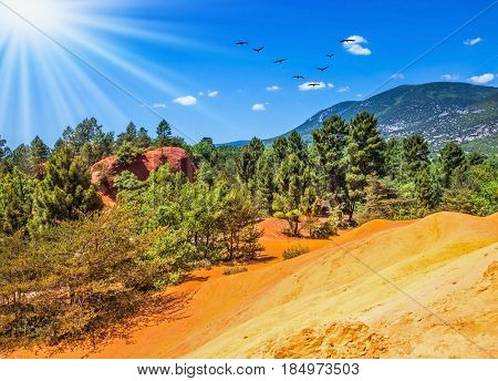 Unique red and orange hills in the province of Languedoc - Roussillon, France. The sun strengthens the color of ocher. The concept of ecological tourism