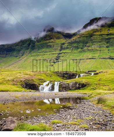 Overcast cold summer day in Iceland. At the foot of the mountain Kirkjoufell powerful waterfalls Kirkjoufellfoss. Concept of extreme and exotic tourism