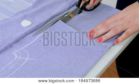 Professional dressmaker, seamstress cutting fabric with scissors at sewing studio. Fashion and tailoring concept