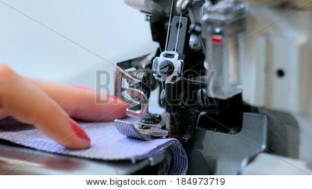 Professional tailor, seamstress using overlocking sewing machine. Fashion and tailoring concept