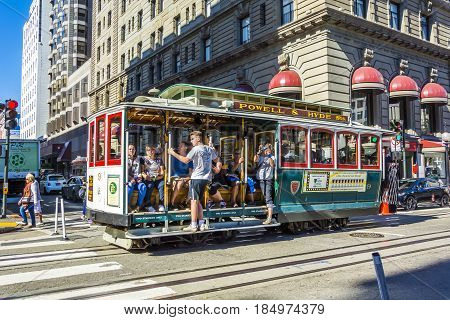 San Francisco CA USA october 2016: Typical cable car train moving in Union Square with tourists in a sunny day