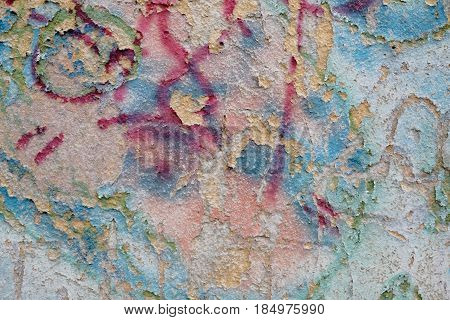 Colorful weathered wall with flushed paint rests. Painted surface background Horizontal shot.
