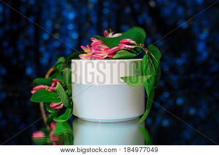 Hand cream with pink flowers over dark blue