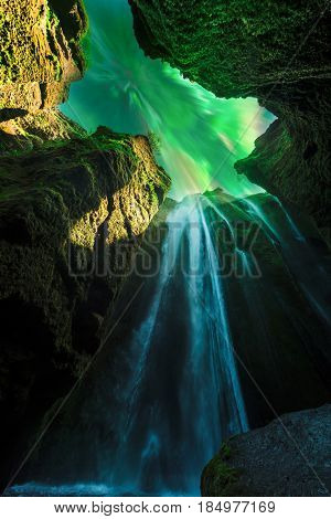 Green aurora light behind unique Gljufrabui waterfall in cave. Iceland, Europe. Courtesy of NASA. Photo collage