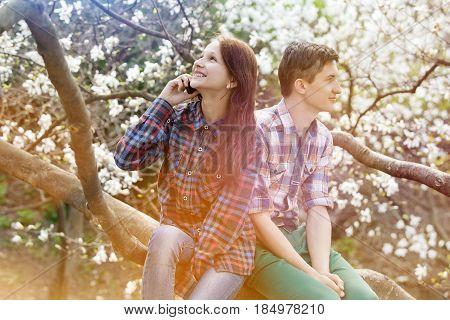 Loving couple sitting on a flowering tree