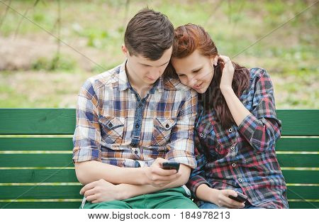 Young couple sitting on the bench at the park watching attentively at mobile phone