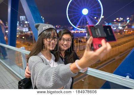HONG KONG - CIRCA DECEMBER, 2015: women taking a selfie in Hong Kong. A selfie is a self-portrait photograph, typically taken with a camera phone held in the hand or supported by a selfie stick.