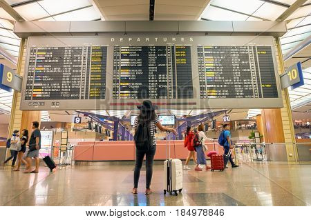 SINGAPORE - CIRCA AUGUST, 2016:  woman looking at timetable departure board in Singapore Changi Airport Terminal 2.