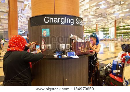 SINGAPORE - CIRCA AUGUST, 2016: people charge gadgets at charging station in Singapore Changi Airport. Changi Airport is one of the largest transportation hubs in Southeast Asia.