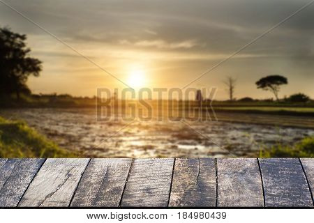 Empty of wooden desk space platform and empty Agriculture field and sunset vintage tone.